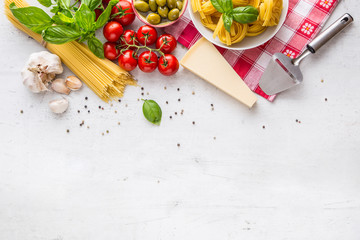 Italian food cuisine and ingredients on white concrete table. Spaghetti Tagliatelle olives olive oil tomatoes parmesan cheese garlic pepper and basil leaves and checkered tablecloth.