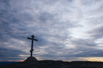 Orthodox Cross at the Top of the Hill with Moving Clouds on Background located in Kandalaksha Russia Cola Penensula Region