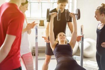frau trainiert ihre arm-muskeln mit unterstützung eines trainers