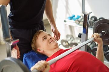 mann stemmt gewichte mit unterstützung eines trainers