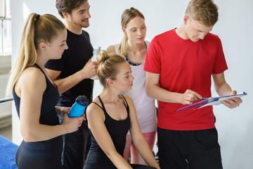 trainer bespricht den plan mit einer gruppe sportler
