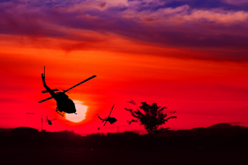 silhouette of helicopter on sunset with copy space add text ( Concept stop hostilities To peace)
