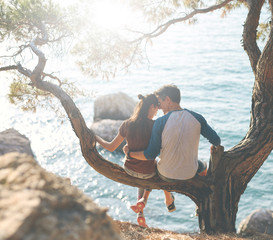 romantic young couple in love together. Happy young couple in love sitting and kissing on a tree branch on sea in background. toned image
