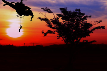 soldier silhouette in rappelling climb down from helicopter on sunset with copy space add text ( Concept stop hostilities To peace)