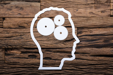 Paper Businessman's Head Outline With Metallic Gears On Table