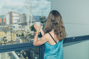 Woman with cup of coffee on balcony in city