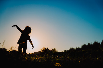silhouette of little girl play at sunset