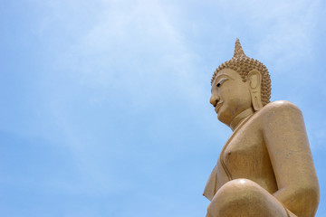 Big giant golden buddha statue in sitting postgure in right side of frame with blue sky in midday