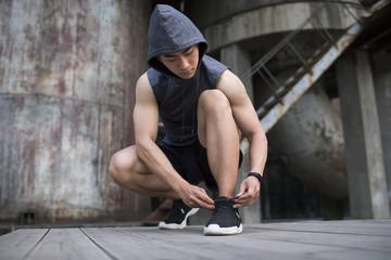 Young man tying shoe lace