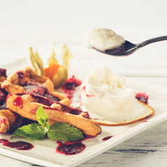 process of eating delicious Viennese waffles with jam and mint on a white plate, light background, toned image