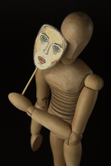 Wooden doll on hinges holds a mask in hands and covers her face on a black background