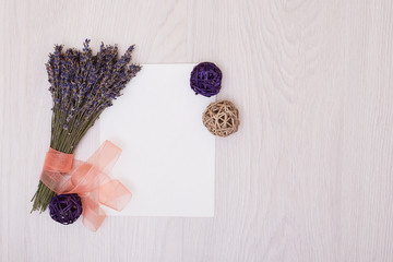 Lavender desk design with flowers on white background top view mock up. White paper postcard