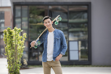 Cheerful young man with skateboard
