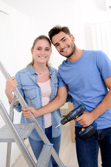 cheerful and happy young couple renovating and painting new home