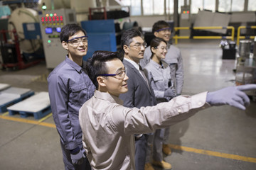 Confident businessman and engineering team in the factory