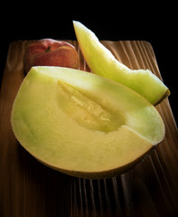Juicy mellow melon and peach on the wooden desk on the black background