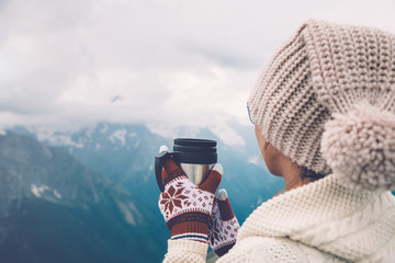 Thermal mug in hands over mountains