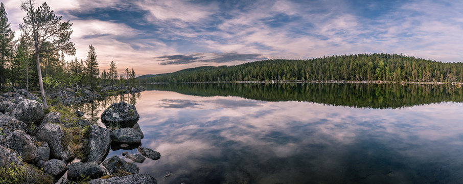 Panorama of calm lake at Lapland in midnight sun time. Rocks in front.