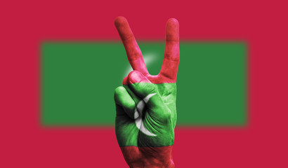 Maldives national flag painted onto a male hand showing a victory, peace, strength sign