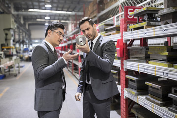 Business people checking machine parts in the factory