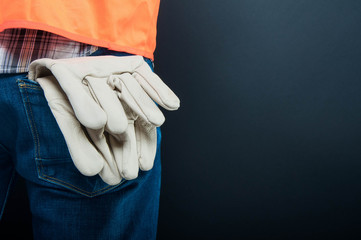 Half close-up of constructor pants with gloves in pocket