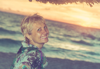Beautiful woman smiling on a sunset beach