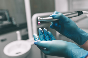 Detail of hand holding dental tools in dental clinic. Dentist Concept.