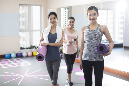 Portrait of young women standing with yoga mats in gym