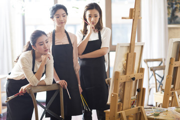 Young women painting in studio