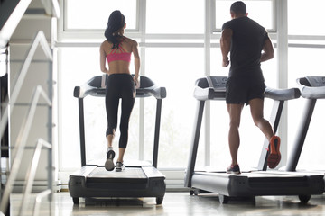 Young couple exercising on treadmills in gym