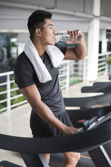 Young man drinking water on a treadmill