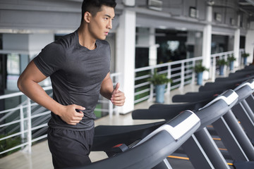 Young man running on treadmill in gym