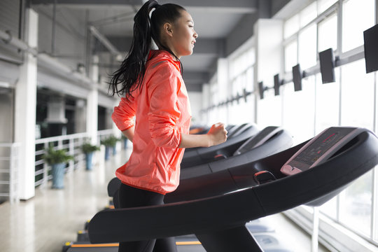 Side view of young woman running on treadmill in gym