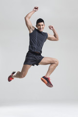 Male athlete jumping against white background