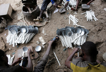 Men work on kitchen skimmers made of recycled sheet metal at a recycling warehouse in Anoumambo, Abidjan