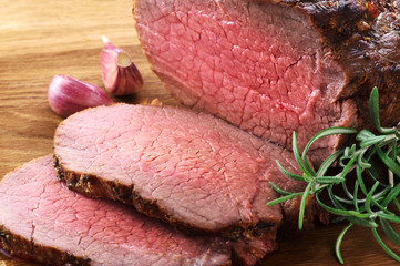 Baked meat, garlic and rosemary on a wooden background. Roast beef.