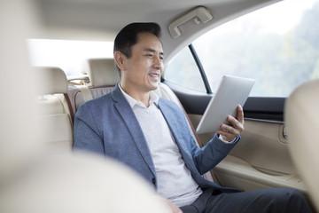 Businessman using digital tablet inside car