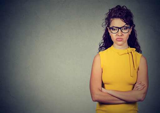 Portrait of angry woman in yellow dress standing with arms folded