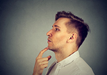Side profile of a thoughtful man standing by the wall