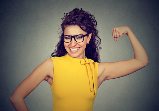 Happy successful strong woman flexing her biceps