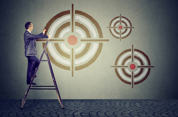 Middle aged business man on a ladder drawing a target on a wall