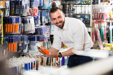 Man selecting sealant in household store .