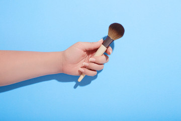 Woman holding makeup brush in her hand on blue background, top view