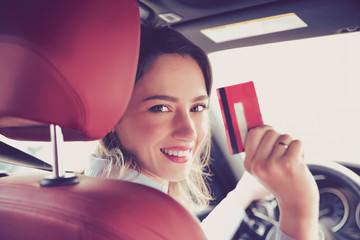 Happy young woman sitting inside her new car showing credit card
