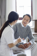 Nursing assistant talking with senior man