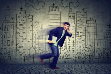 Young man running late to work talking on mobile phone
