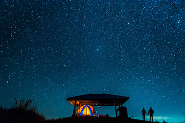 Silhouette of romantic couple watching sky full of stars on mountain.  Glowing tent and lovers with a starry night view.
