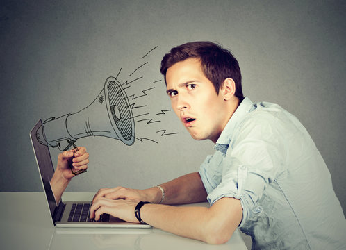 Anxious man sitting at table using working on a computer with megaphone poking out from a laptop screen