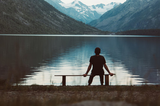 A lonely man sitting on the bench in front of the lake