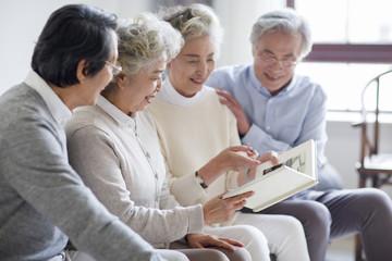 Happy senior friends looking at photo album